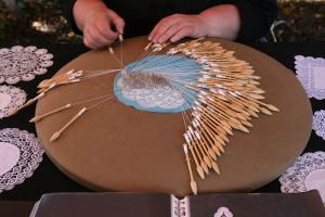 Making bobbin lace; image from wikimedia commons